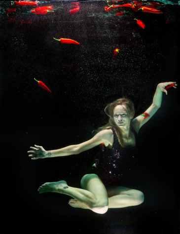 woman underwater wearing black one piece swimsuit